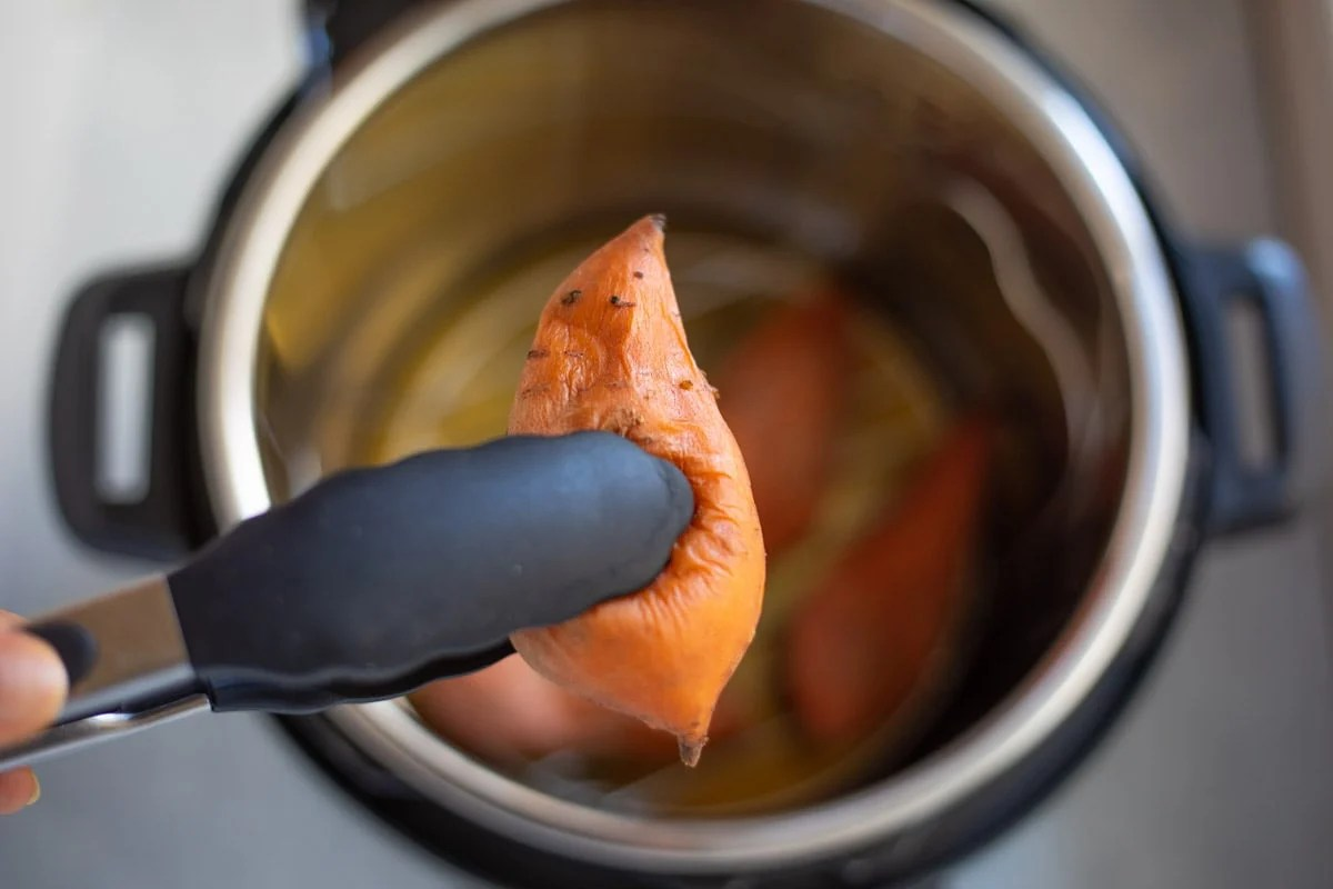 A cooked sweet potato being picked out of the instant pot with tongs