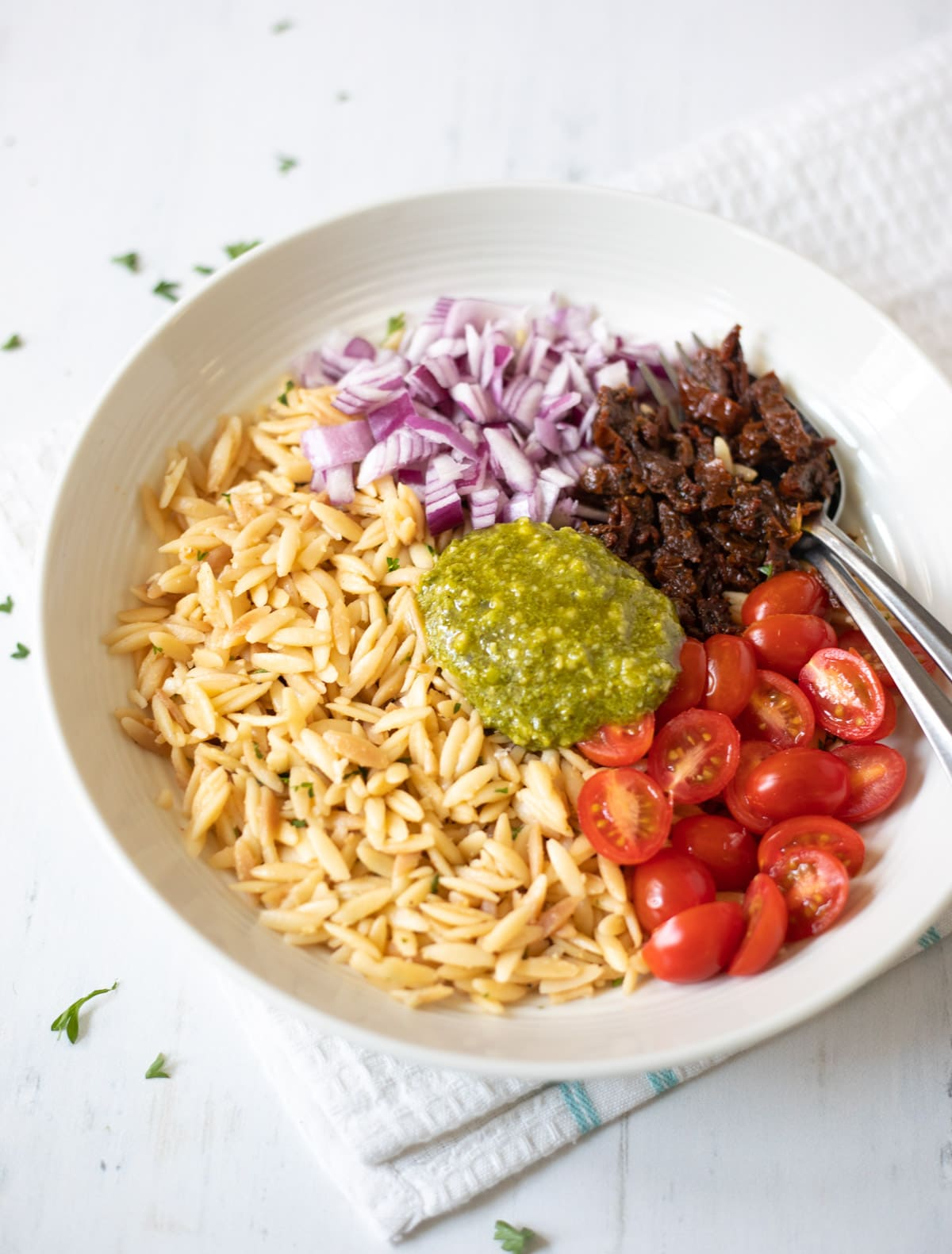 ingredients in a bowl to make salad such as orzo, tomatoes, onions and pesto