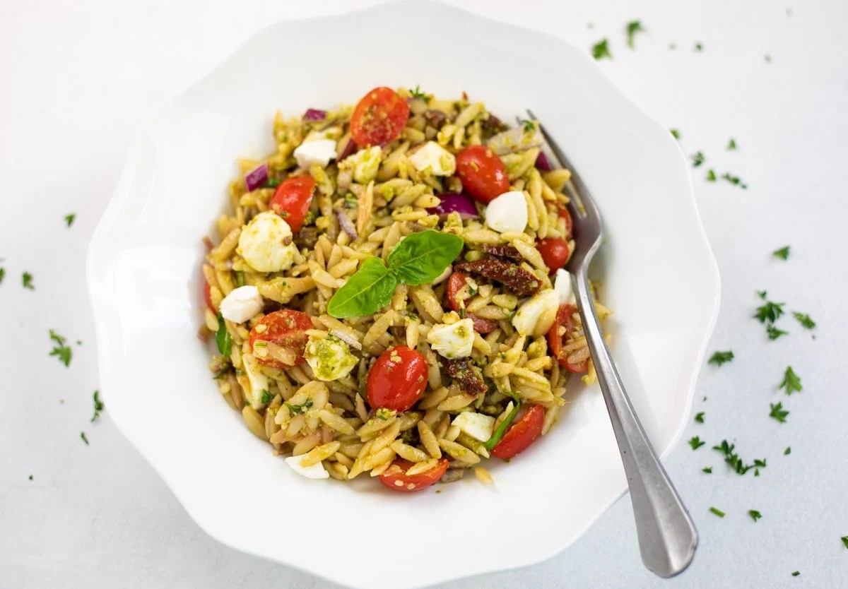 Pesto pasta salad in a white bowl with a fork