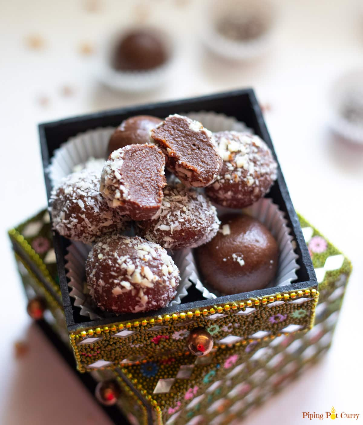A cut chocolate truffle over other balls in a small decorated box
