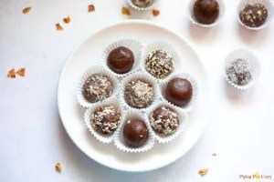 Chocolate balls covered in some chopped nuts in a white plate and spread around.