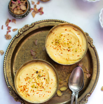 2 small bowls of Indian Mango Shrikhand dessert garnished with saffron and pistachios.