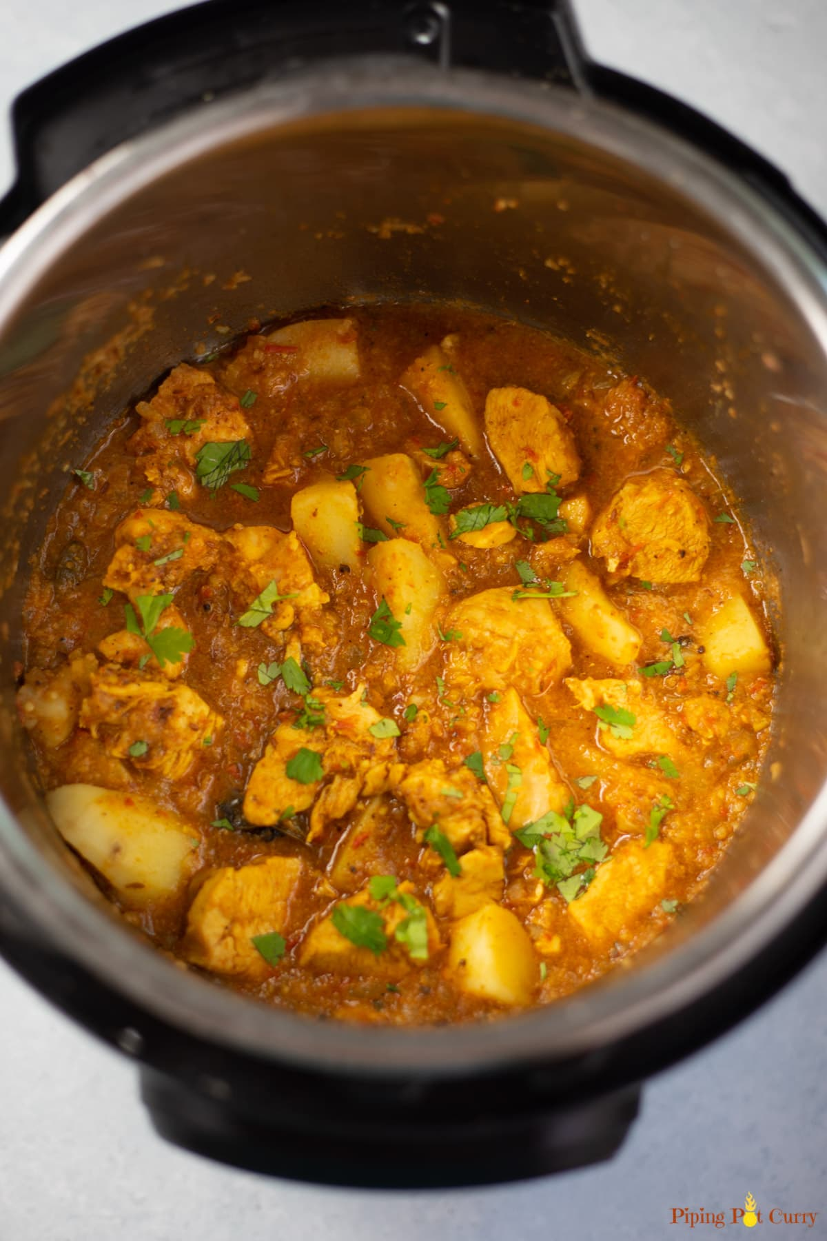 Indian Chicken & potato curry in the instant pot garnished with cilantro