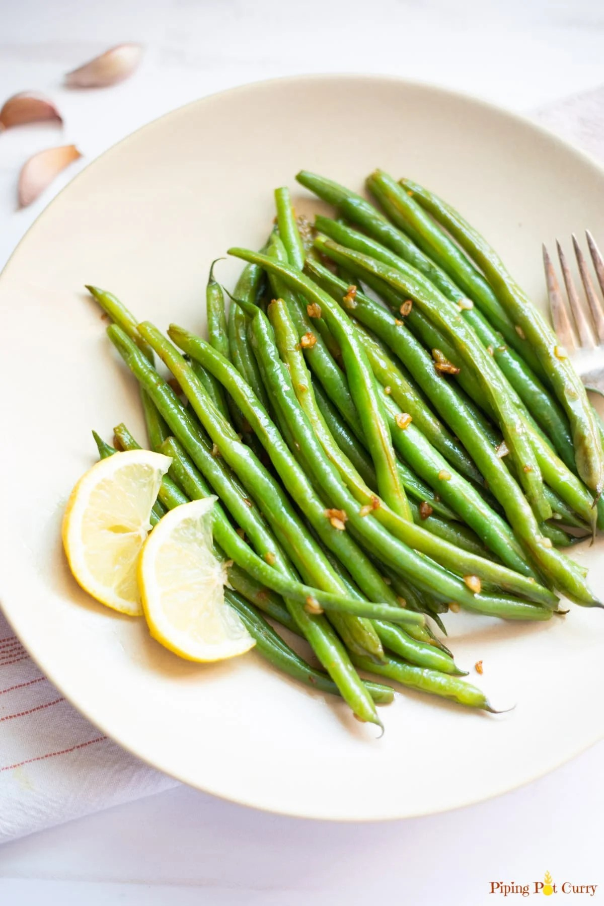 Lemon Garlic Green Beans in a plate with 2 pieces of sliced lemon