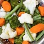 a medley of steamed vegetables in a steamer basket