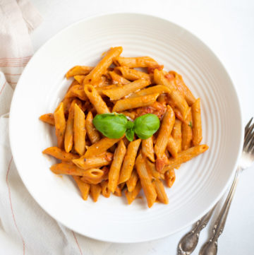 penne pasta in red sauce garnished with basil leaves in a white bowl