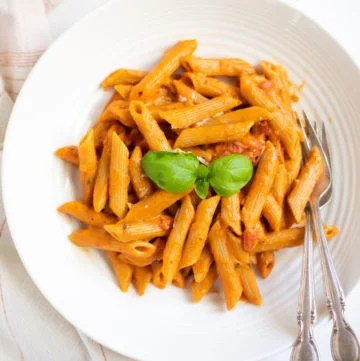 Penne pasta in red tomato sauce in a white bowl garnished with basil leaves