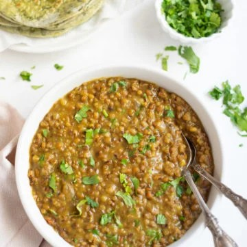 Moth lentils in a white bowl with cilantro and roti