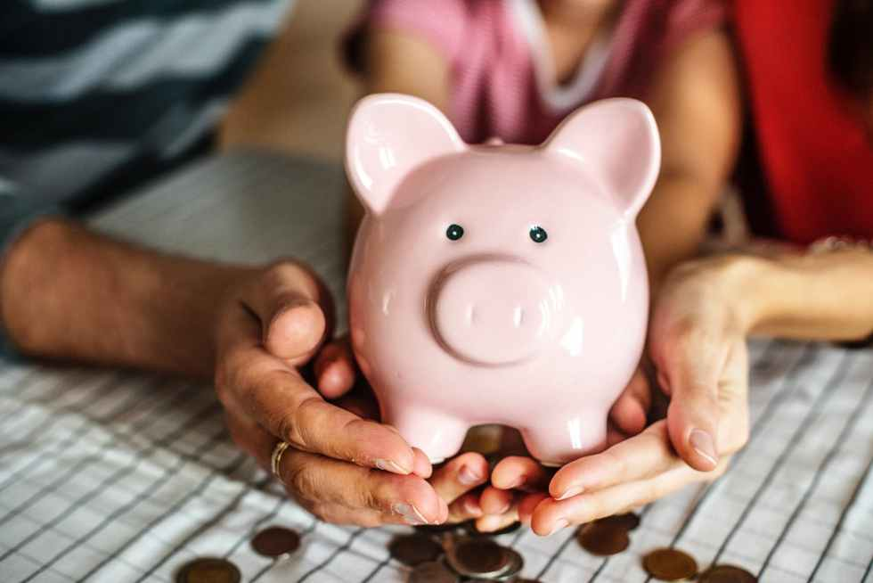 person holding pink piggy coin bank