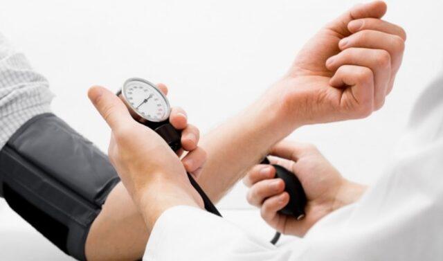 Uma foto de um homem medindo a sua pressão para prevenir a hipertensão