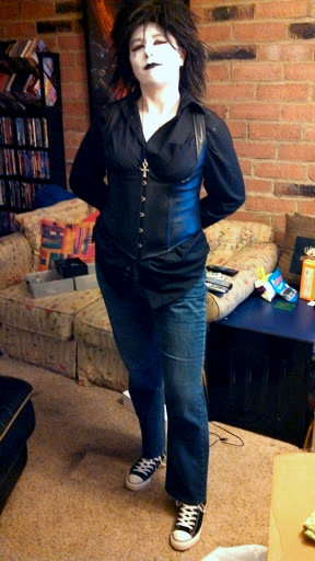 Myself as Death from The Sandman comic book series wearing a men's black shirt, black leather underbust corset, blue jeans, and black Chuck Taylor Hi-tops.