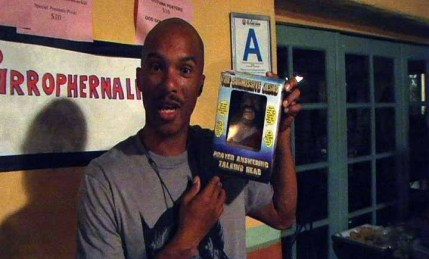 "Damon Evans holding a Submissive Jesus toy at the premiere of ""The God Complex."""
