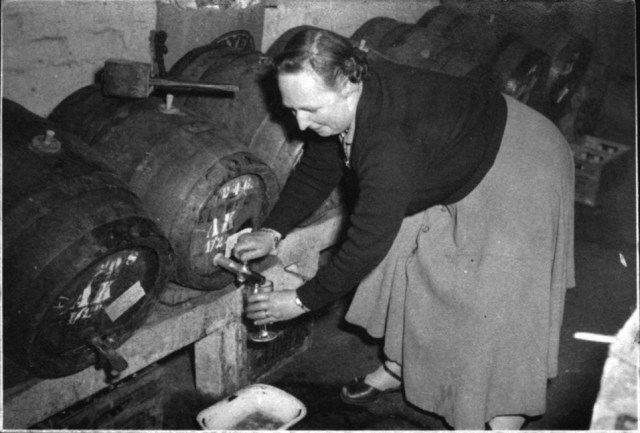 1950  May Cook tapping a pint. The drayman from the brewery (Greens and Flowers) delivered the barrels on Tuesdays and set them up on stands in the taproom. The 18 gallon barrels were called kilderkins and were arranged in order: mild at one end and bitter at the other. Lager was not sold in the Fox in the 1950s. A windpeg was hammered into the top of the barrel to let in the air and a tap knocked into the front to let the beer out.