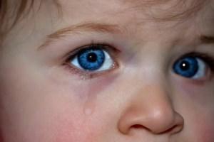 青い目の小さい子供が涙を流している