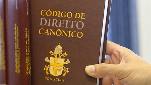 Mão pegando o Código de Direito Canônico de uma estante