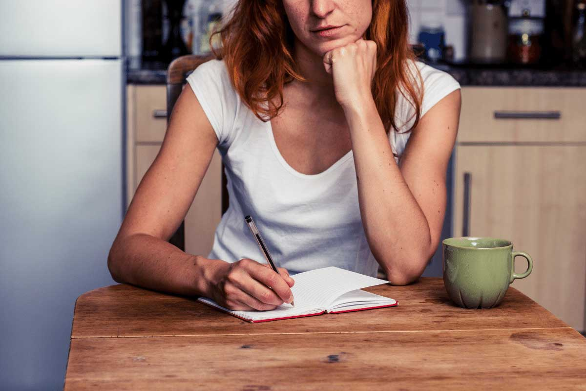 Woman sitting at a kitchen table with her left hand under her chin thinking about what to write on a sheet of paper