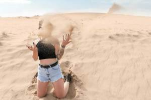 women kneeling on a sand dune throwing sand up in the air upset that she has vaginal dryness due to clomid and is trying to increase cervical mucus