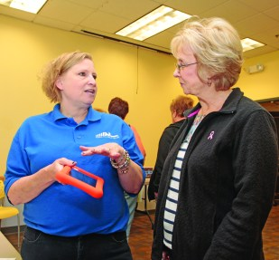 "Children's librarian Jeanne Bondi explains the benefits of the ""Playaway"" device to Connie Johnston. Photo by Chuck LeClaire"