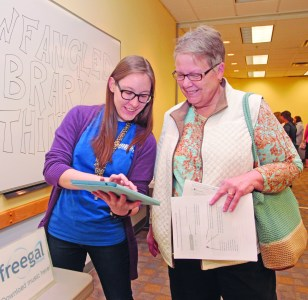 "Raeann MacNeill explains how to download the latest Adele songs via the ""freegal"" music app to Margaret Daniels of Wexford. Photo by Chuck LeClaire"