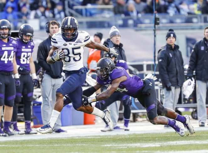 Jester Weah #85 of the Pittsburgh Panthers makes a catch for a touchdown as Montre Hartage #24 of the Northwestern Wildcats attempts to tackle. The Northwestern Wildcats defeated the Pittsburgh Panthers 31-24 in the 2016 New Era Pinstripe Bowl at Yankee Stadium on Wednesday, December 28, 2016.