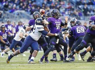 Shakir Soto #52 of the Pittsburgh Panthers puts pressure on Clayton Thorson #18 of the Northwestern Wildcats as he throws. The Northwestern Wildcats defeated the Pittsburgh Panthers 31-24 in the 2016 New Era Pinstripe Bowl at Yankee Stadium on Wednesday, December 28, 2016.