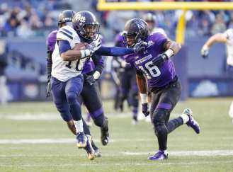 Quadree Henderson #10 of the Pittsburgh Panthers puts a stiff arm on Godwin Igwebuike #16 of the Northwestern Wildcats of the Northwestern WildcatsThe Northwestern Wildcats defeated the Pittsburgh Panthers 31-24 in the 2016 New Era Pinstripe Bowl at Yankee Stadium on Wednesday, December 28, 2016.