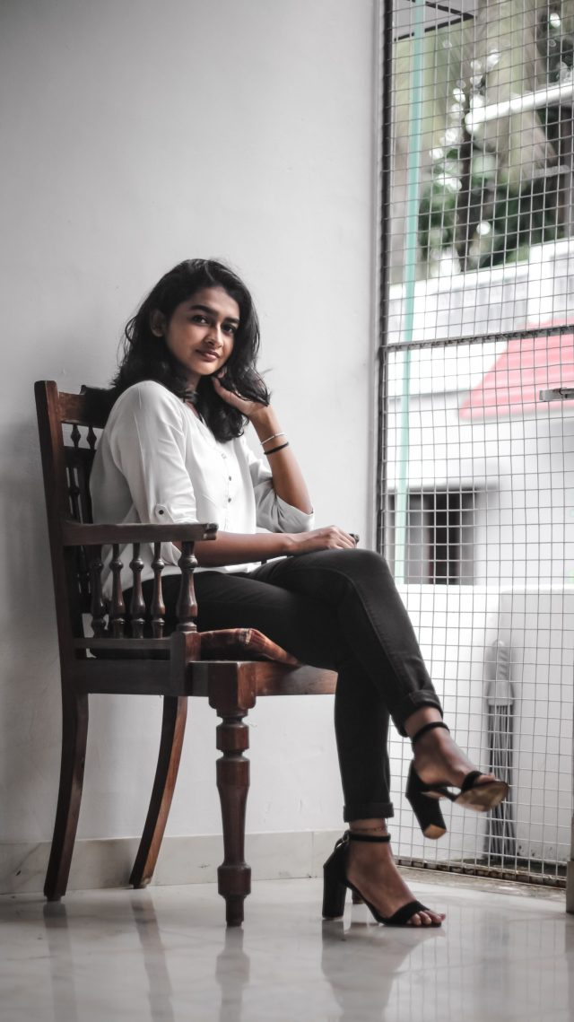 A girl posing while sitting on a chair