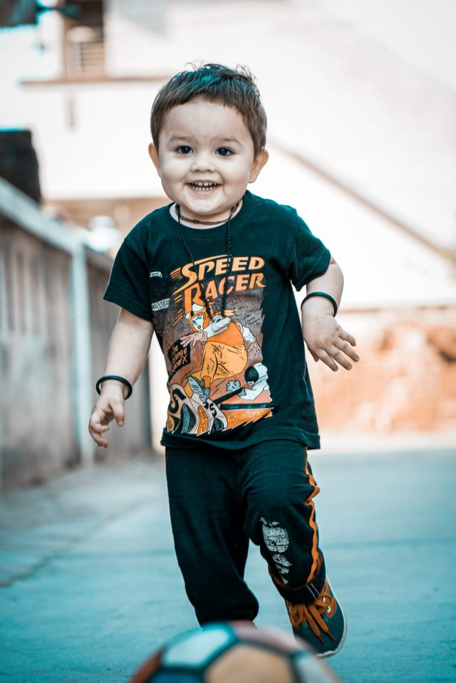 Happy kid running with soccer ball