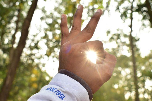 Sun rays through fingers