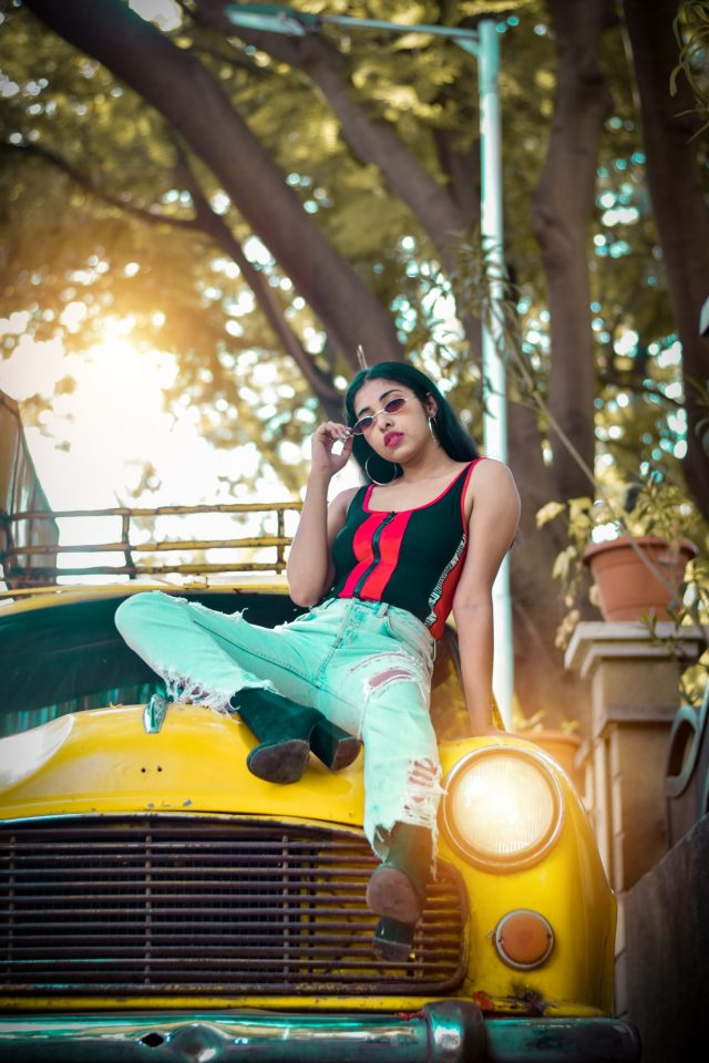 A girl model posing on a taxi.