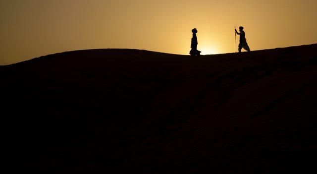 Two men walking in the desert.