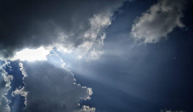 sun shining behind clouds
