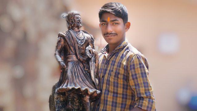 A boy near statue of Shivaji Maharaj