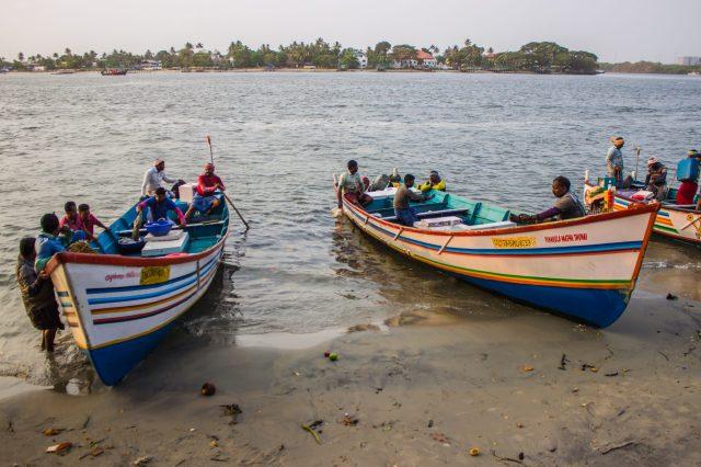 Fishermen with boats at riverbank