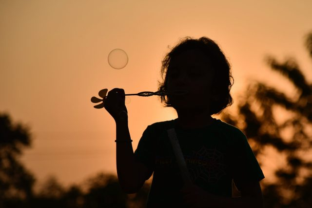 silhouette of girl blowing bubbles