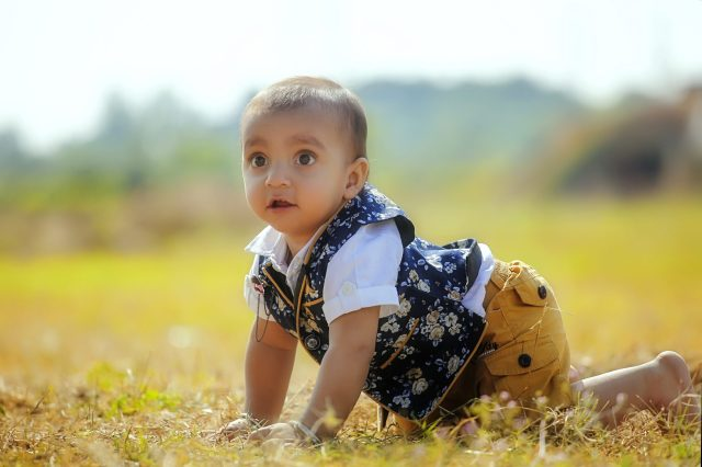 kid crawling in grass
