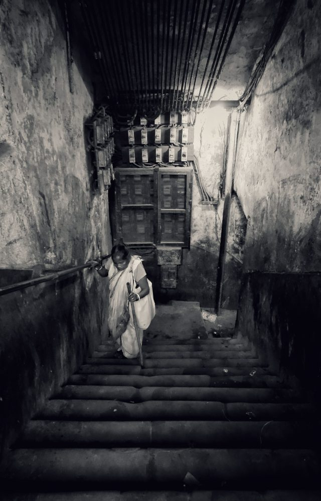 An old woman climbing stairs