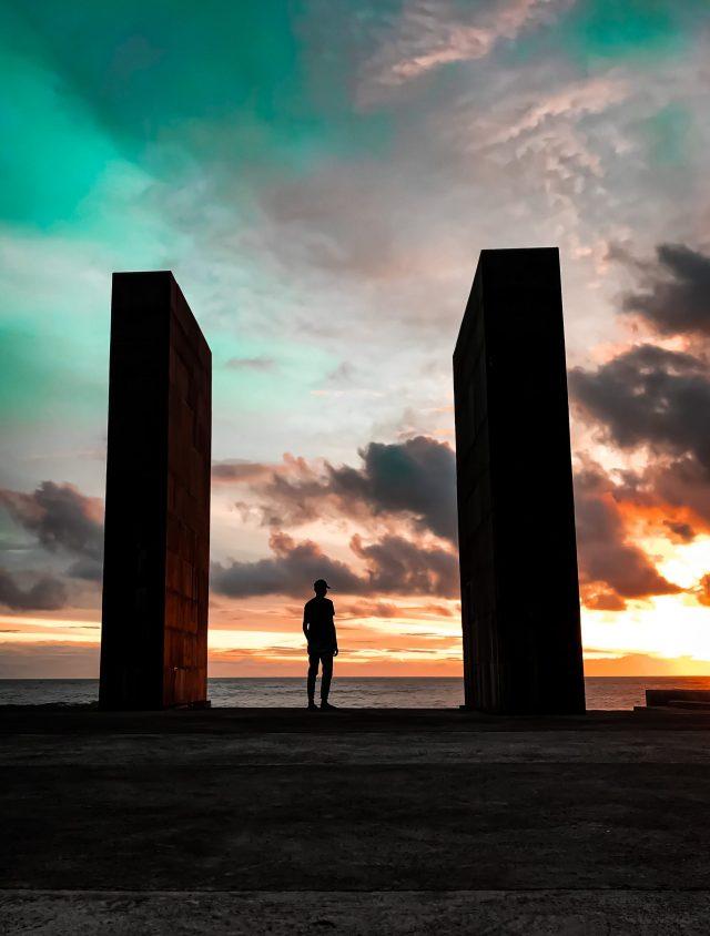 Guy standing in between two pillars at beach