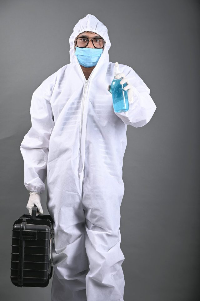 Man wearing PPE kit and holding Sanitizer in hand