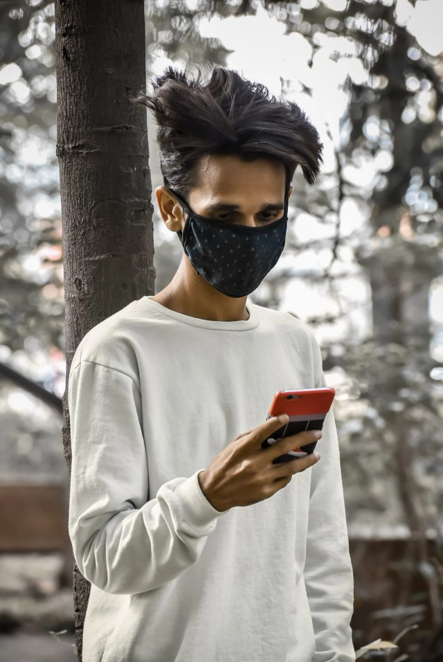 Boy using phone while wearing mask