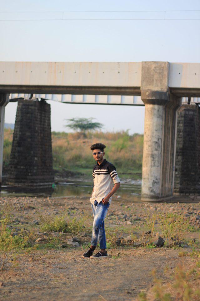 Boy standing on a damp area near bridge