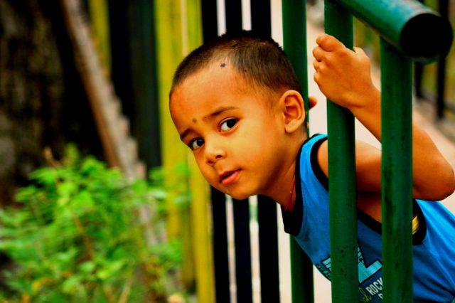 Little boy peeking through the railing