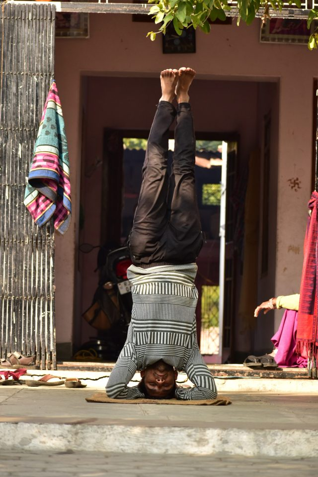 A man practicing head stand Yoga pose