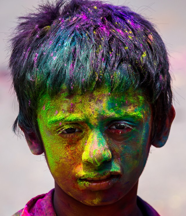 A child's face painted with Holi colors