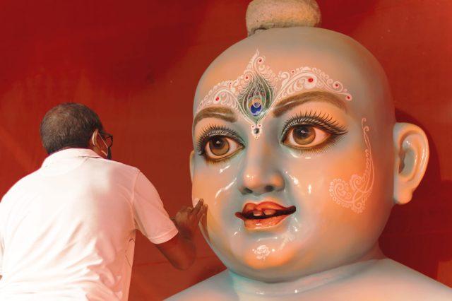 A man near a statue of Lord Krishna