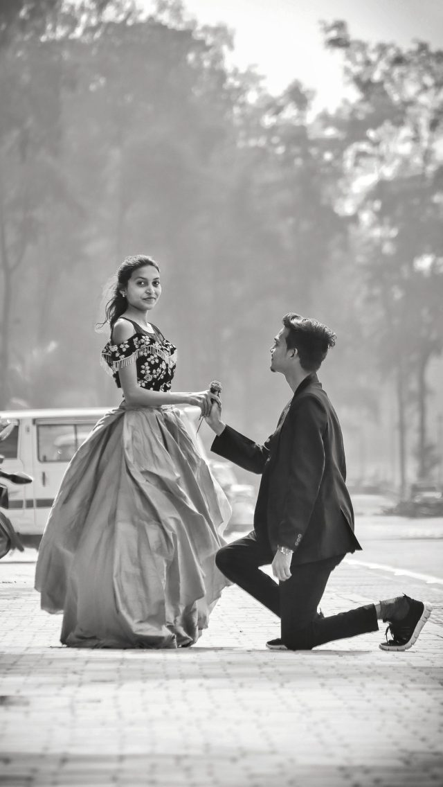 Boy purposing to a girl on the road