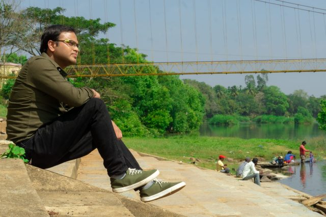 Male model sitting on the riverside enjoying the view
