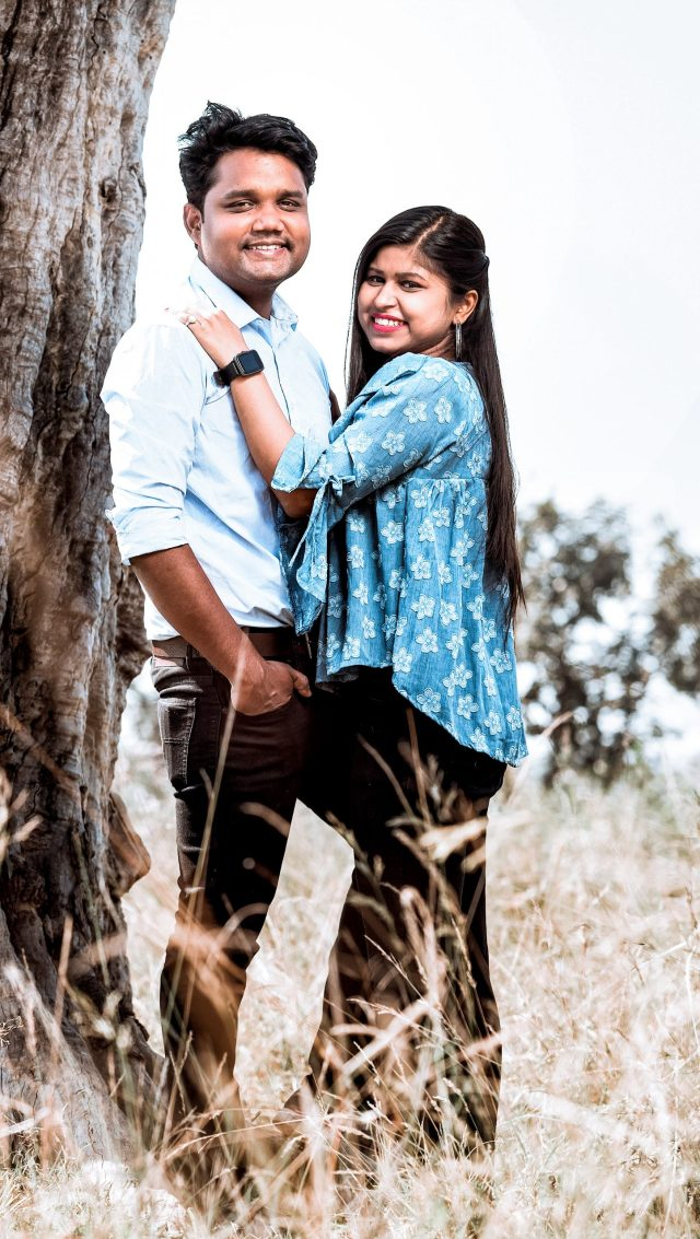Couple posing by the side of tree