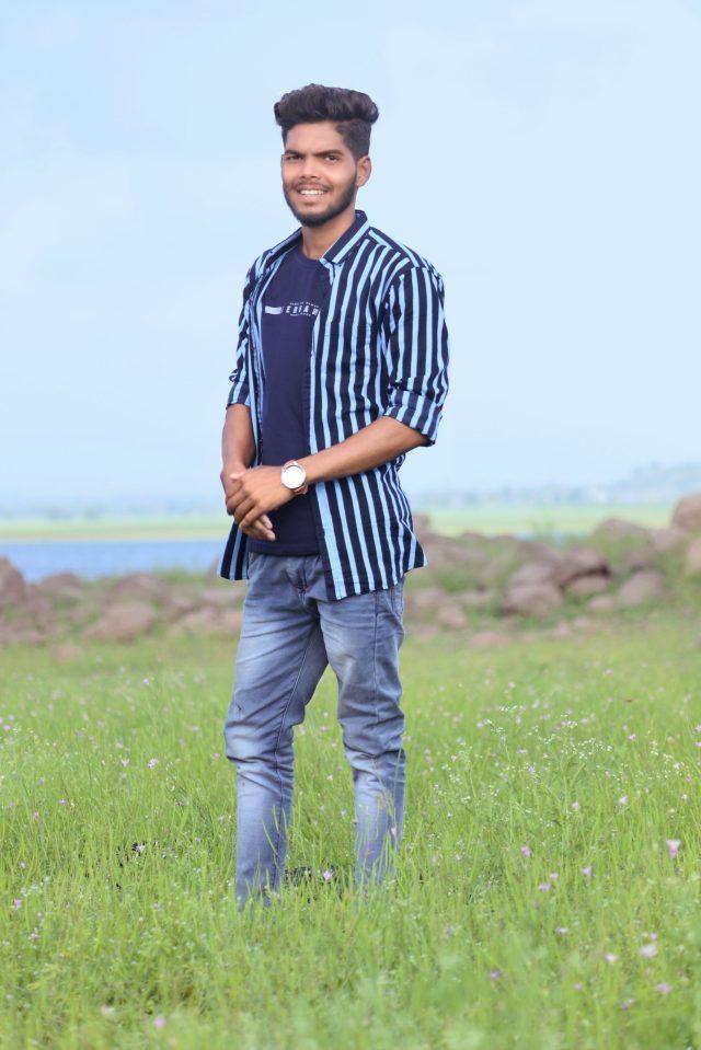 Stylish young boy posing in the grassy farm