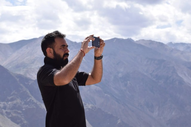 Young man capturing mountains